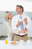 Mujer que abraza a un hombre feliz de detrás en cocina Foto de archivo