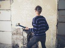 Mujer que abre la chimenea con el martillo de trineo Foto de archivo libre de regalías