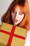 Mujer que abre un presente Fotos de archivo