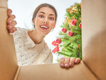 Mujer que abre un regalo de Navidad Fotografía de archivo