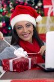 Mujer que abre un regalo el noche de la Navidad Imágenes de archivo libres de regalías