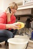 Mujer que absorbe el fregadero que se escapa Imagen de archivo libre de regalías