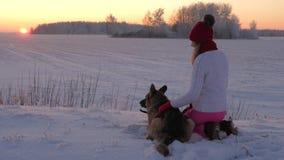 Mujer que acaricia encariñado el perro que se sienta en la nieve en una tarde del invierno en la puesta del sol almacen de video