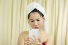 Mujer que actúa que juega en el teléfono ella lleva una falda para cubrir su pecho después del pelo del lavado, envuelto en to fotografía de archivo