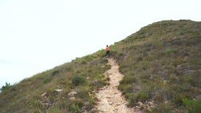 Mujer que activa en el camino de la montaña Muchacha del deporte que ejercita afuera en montañas metrajes