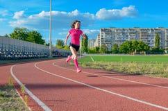 Mujer que activa en la pista, corriendo en estadio Fotos de archivo