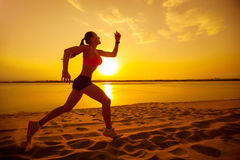 Mujer que activa en la playa en la puesta del sol Fotos de archivo libres de regalías