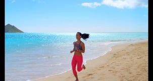 Mujer que activa en la playa 4k almacen de metraje de vídeo
