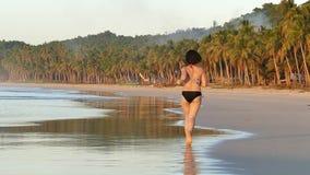 Mujer que activa en la playa en la puesta del sol hermosa almacen de metraje de vídeo