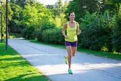 Mujer que activa feliz que corre en parque Imagenes de archivo