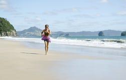 Mujer que activa a lo largo de una playa hermosa. Imagen de archivo libre de regalías