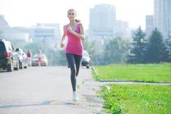 Mujer que activa que corre en parque de la ciudad Imágenes de archivo libres de regalías