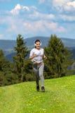 Mujer que activa que corre en sol en día de verano hermoso y que escucha una música en auriculares Fotografía de archivo