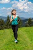 Mujer que activa que corre en sol en día de verano hermoso y que escucha una música en auriculares Imagen de archivo