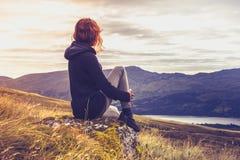 Mujer que admira puesta del sol del top de la montaña