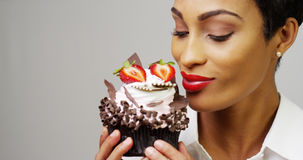 Mujer que admira una magdalena de lujo del postre con el chocolate y las fresas Fotos de archivo