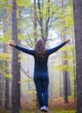 Mujer que adora con los brazos abiertos en el bosque en otoño Imágenes de archivo libres de regalías