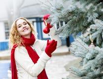 Mujer que adorna el árbol de navidad afuera fotos de archivo