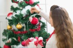 Mujer que adorna el árbol de navidad. Visión trasera Fotos de archivo libres de regalías