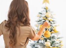 Mujer que adorna el árbol de navidad. vista posterior Fotos de archivo