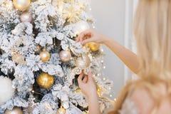 Mujer que adorna el árbol del Año Nuevo Juguete del árbol de navidad bajo la forma de cochecito Imagen de archivo