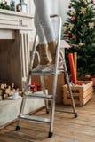 Mujer que adorna el sitio para la Navidad en la escalera de mano Fotografía de archivo