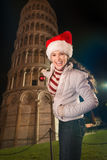 Mujer que adorna la torre inclinada de Pisa con la bola de la Navidad Imágenes de archivo libres de regalías