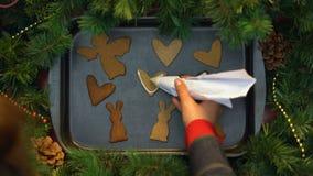Mujer que adorna las galletas del pan de jengibre con la crema, hornada de la Navidad, preparación almacen de video