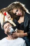 Mujer que afeita al hombre barbudo hermoso Imagen de archivo