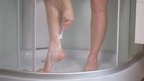 Mujer que afeita las piernas en el cuarto de baño metrajes