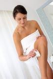 Mujer que afeita sus piernas Imágenes de archivo libres de regalías