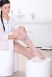 Mujer que afeita sus piernas Imagen de archivo libre de regalías