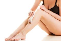 Mujer que afeita sus piernas con la maquinilla de afeitar eléctrica Foto de archivo