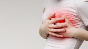 Mujer que agarra su pecho, dolor agudo como ataque del corazón posible fotos de archivo