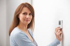 Mujer que ajusta control del termóstato de la calefacción central Fotos de archivo libres de regalías