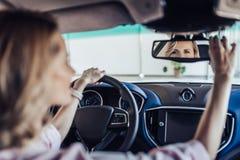 Mujer que ajusta el espejo de la vista posterior en coche fotos de archivo