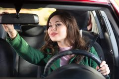 Mujer que ajusta el espejo de la vista posterior de un coche fotografía de archivo libre de regalías