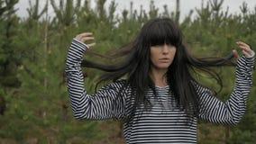 Mujer que ajusta el pelo en bosque metrajes