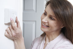 Mujer que ajusta el termóstato en control de la calefacción central Foto de archivo