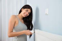 Mujer que ajusta el termóstato en el radiador Fotos de archivo