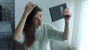 Mujer que ajusta su pelo usando la tableta como espejo almacen de video