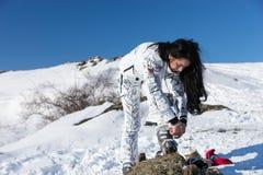 Mujer que ajusta a su Ski Gear en la nieve Imagenes de archivo