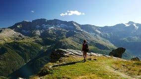 Mujer que alcanza el top de la montaña en paisaje rocoso de la mucha altitud con el glaciar y el pico en el fondo Aventuras del v almacen de metraje de vídeo