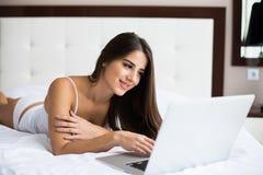 mujer que alcanza en sus medios sociales como ella se relaja en cama con un ordenador portátil en un día perezoso imagen de archivo