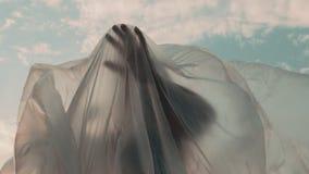 Mujer que alcanza hacia fuera con su mano debajo de hoja plástica almacen de video