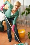 Mujer que aljofifa el suelo en su hogar Foto de archivo libre de regalías