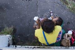 Mujer que amamanta a un niño que vende velas en la yarda de la iglesia Foto de archivo