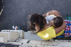 Mujer que amamanta a un niño que vende velas en la yarda de la iglesia Fotos de archivo libres de regalías