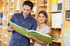 Mujer que analiza el libro grande con el hombre en tienda Imagenes de archivo