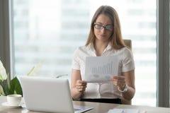 Mujer que analiza indicadores financieros hacia abajo Fotografía de archivo